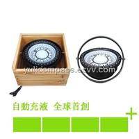 plastic marine compass on wooden box